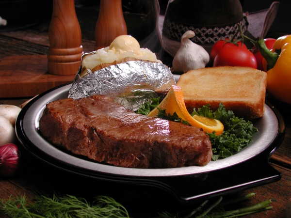 steak with baked potato and toast with vegetables around the plate