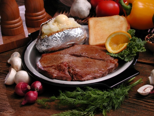 steak with baked potato and toast with vegetables